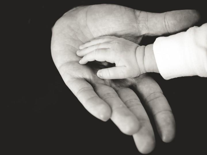 dłoń niemowlaka w silnej męskiej dłoni