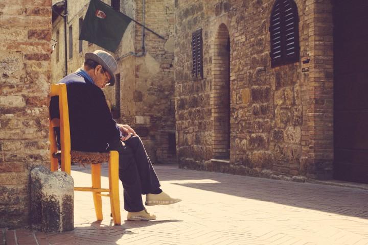 staruszek siedzący na rogu ulicy