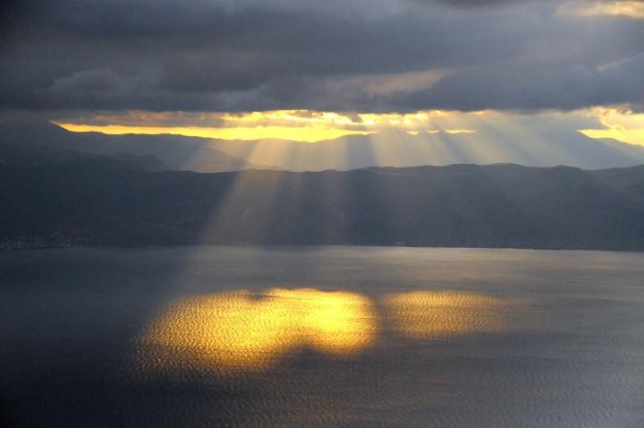 promienie słońca przebijające się przez niskie chmury nad wodą