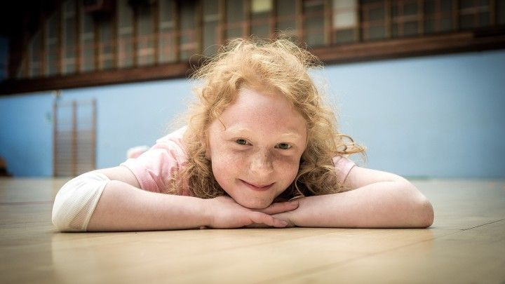 szczęśliwa, piegowata dziewczynka leżąca na podłodze w sali gimnastycznej