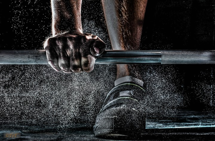 męska dłoń z gryfem na treningu siłowym