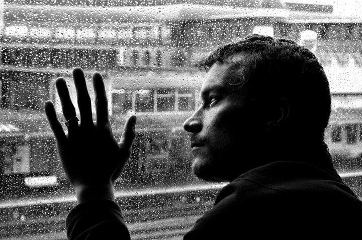 depresja samotny mężczyzna oparty o szybę i wpatrzony w deszcz