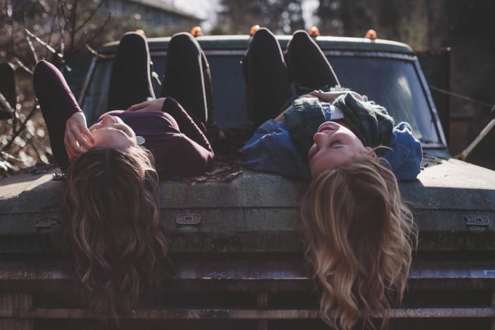 dwie młode kobiety smiejące się, rozmawiające i leżące na masce auta