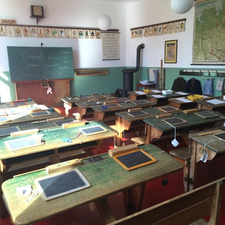 klasa szkolna z tablicą, stołami i tabliczkami
