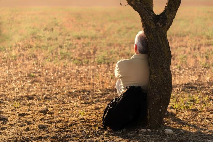 zamyslony samotny mężczyzna oparty o pień drzewa