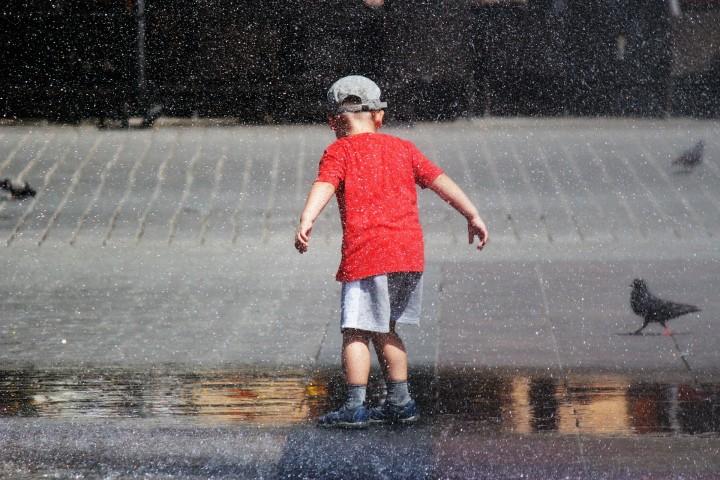mały chłopiec biegający po placu w kroplach fontanny