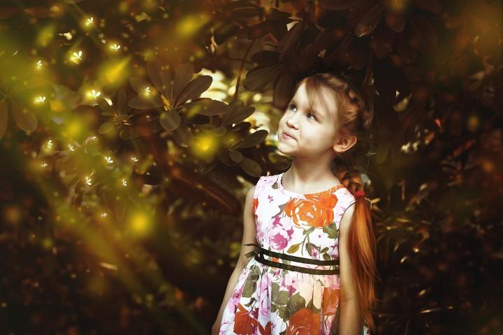 piegowata dziewczynka wpatrzona w promienie słońca