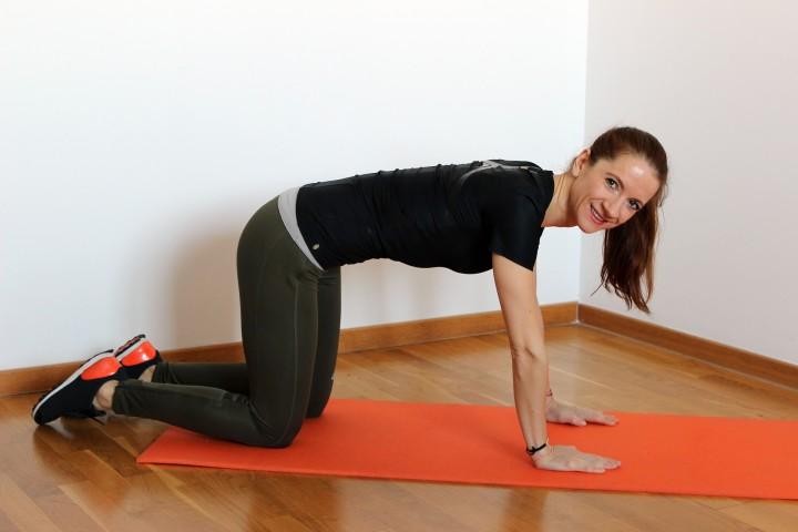 młoda kobieta w trakcie ćwiczeń w klęku podpartym