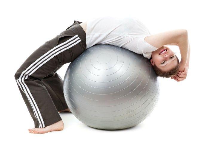 młoda kobieta ćwicząca na piłce gimnastycznej