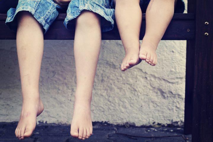 nogi dzieci siedzących na murku nad wodą