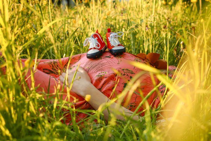 kobieta ciężarna odpoczywająca w trawie