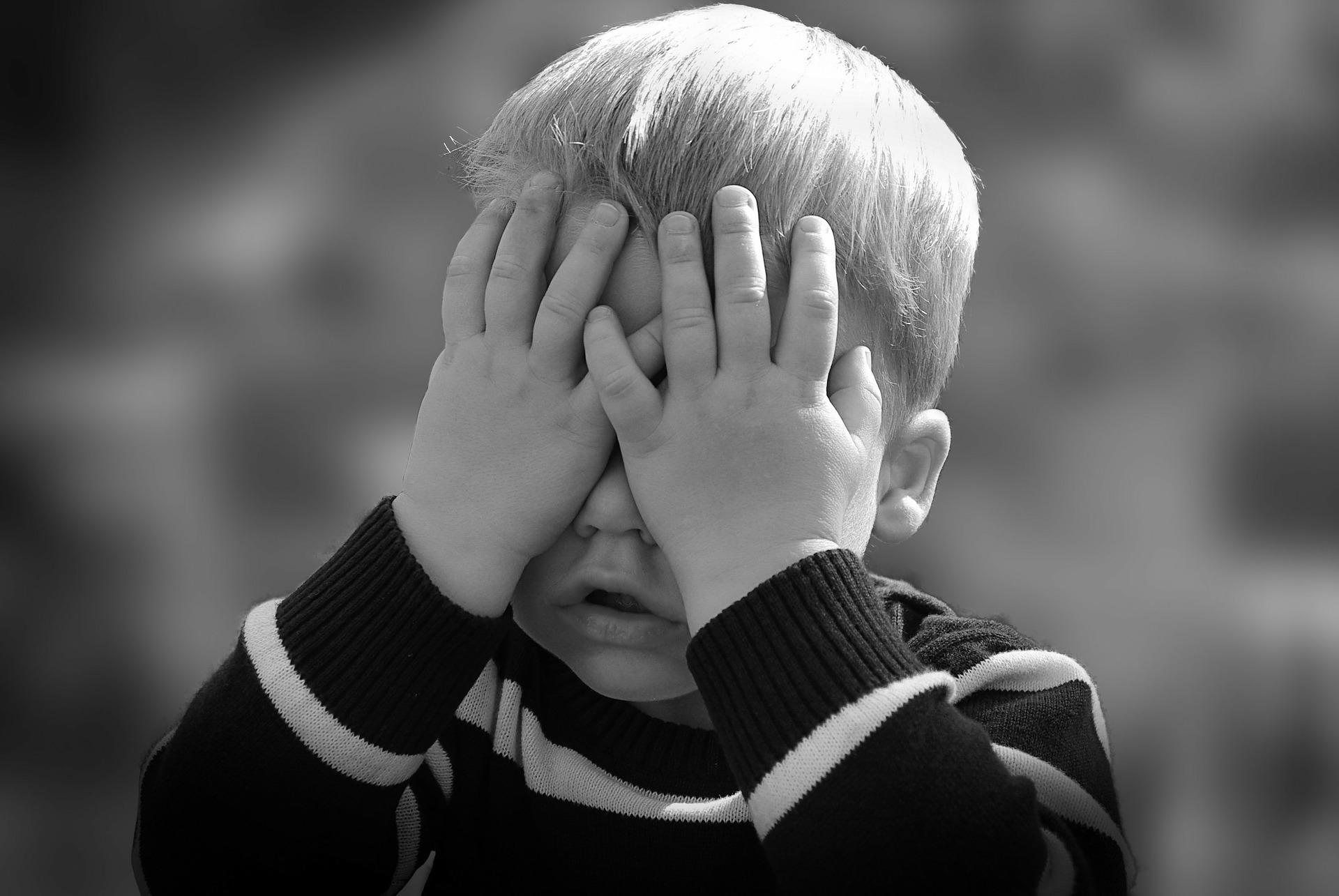 mały chłopiec z zasłoniętymi oczami