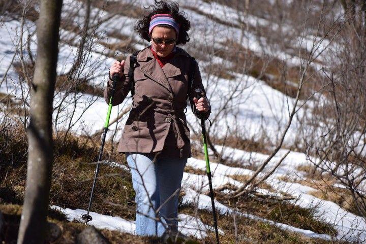 kobieta z kijami na sniegu uprawiająca Nordic Walking