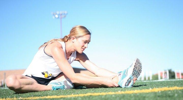 kobieta rozciagająca mięśnie na boisku