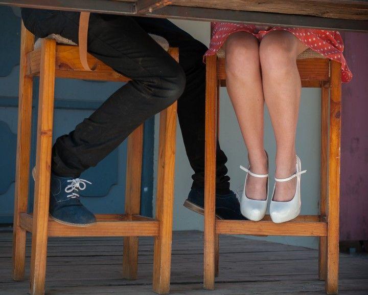 zgrabne nogi kobirty i mężczyzny siedzących razem przy stole