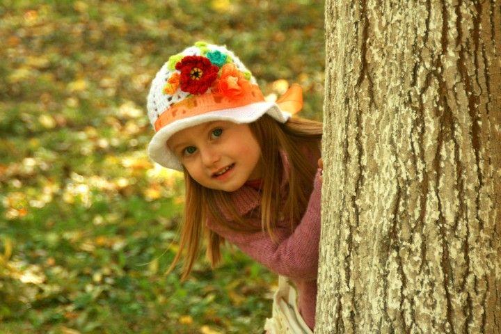mała dziewczynka w kolorowym kapeluszu chowająca się za pniem drzewa