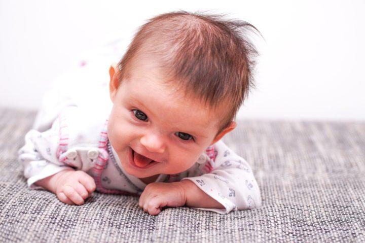 wesołe niemowle lezace na brzuszku