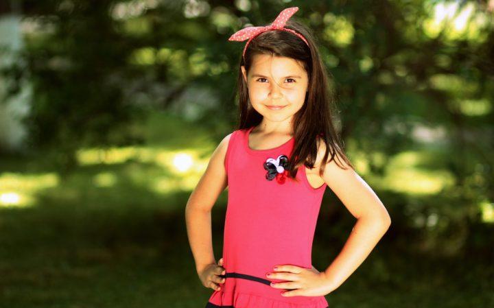 ładna, usmiuechnięta dziewczynka w różowej sukience