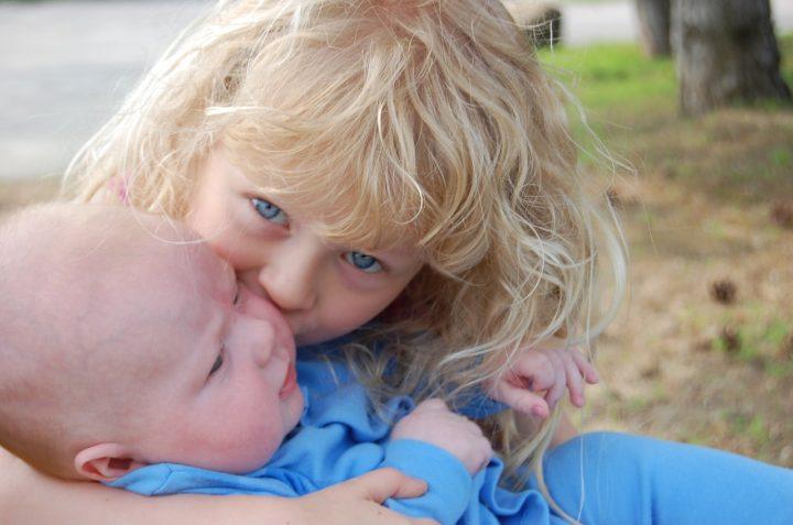 rodzeństwo- mała dziewczynka przytula brata