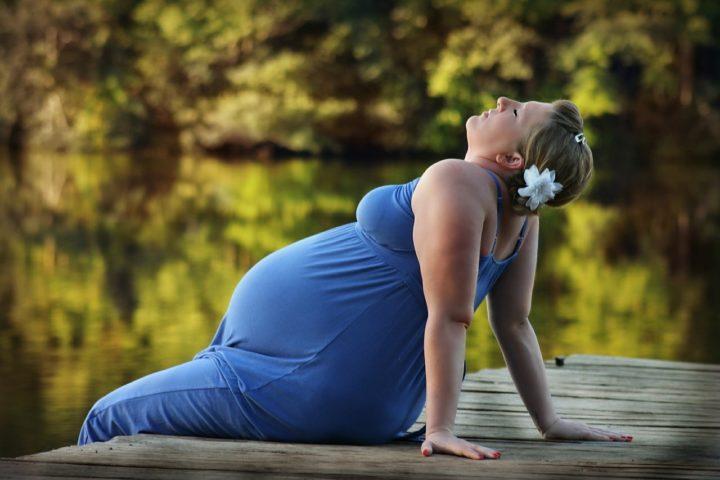kobieta w ciąży siedząca nad wodą na pomoście