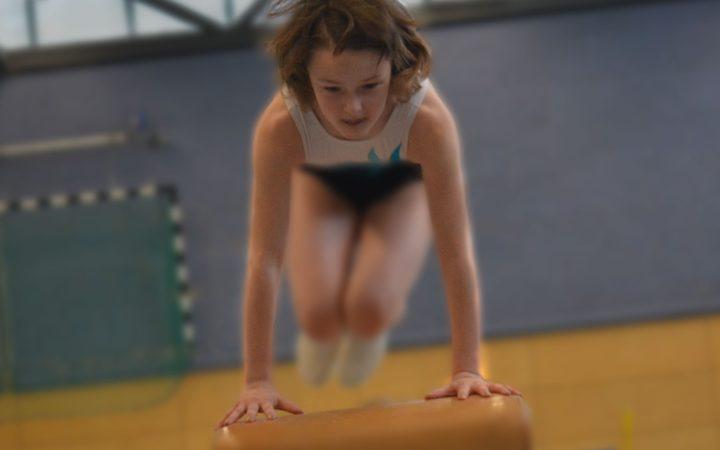 mała dziewczynka skacząca przez kozła