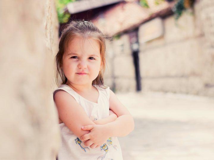 mała dziewczynka oparta o murek
